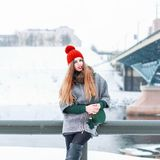 Το νέο όμορφο κορίτσι σε ένα παλτό γουνών και μια πλεκτή ΚΑΠ κάθεται σε ένα β Στοκ φωτογραφία με δικαίωμα ελεύθερης χρήσης