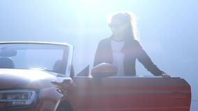 Το νέο όμορφο κορίτσι στα μαύρα γυαλιά και ένα σακάκι δέρματος εμφανίζεται και κάθεται σε ένα κόκκινο μετατρέψιμο ενάντια στο σκη απόθεμα βίντεο