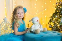 Το νέο όμορφο κορίτσι στην μπλε άσπρη κομψή συνεδρίαση φορεμάτων βραδιού στο πάτωμα κοντά στο χριστουγεννιάτικο δέντρο και παρουσ Στοκ Εικόνες
