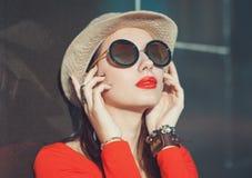 Το νέο όμορφο κορίτσι στο καπέλο και τα γυαλιά ηλίου απολαμβάνουν το φως του ήλιου Στοκ εικόνα με δικαίωμα ελεύθερης χρήσης