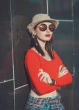 Το νέο όμορφο κορίτσι στο καπέλο και τα γυαλιά ηλίου απολαμβάνουν το φως του ήλιου Στοκ Εικόνα