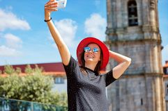 Το νέο όμορφο κορίτσι στο κόκκινο καπέλο παίρνει selfie στοκ εικόνες