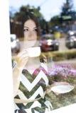 Το νέο όμορφο κορίτσι στο ποτήρι επιδεικνύει έναν καφέ, ηλιόλουστη ημέρα, που κρατά την κούπα του τσαγιού Στοκ φωτογραφία με δικαίωμα ελεύθερης χρήσης