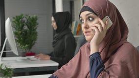 Το νέο όμορφο κορίτσι στο ρόδινο hijab κάθεται στο γραφείο και μιλά στο smartphone, γέλιο 60 fps φιλμ μικρού μήκους
