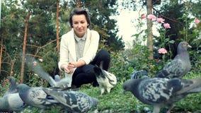 Το νέο όμορφο κορίτσι ταΐζει τα περιστέρια στο πάρκο Κοπάδι των πουλιών που τρώνε μια φραντζόλα υπαίθρια απόθεμα βίντεο