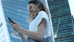 Το νέο όμορφο κορίτσι χρησιμοποιεί ένα smartphone στο υπόβαθρο των ουρανοξυστών απόθεμα βίντεο