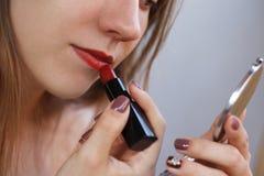 Το νέο όμορφο κορίτσι χρωματίζει τα χείλια της με το κόκκινα κραγιόν και το holdi Στοκ Εικόνα