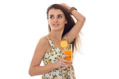 Το νέο όμορφο κορίτσι brunette σε sarafan με το floral σχέδιο πίνει το πορτοκαλί κοκτέιλ και φαίνεται κατά μέρος απομονωμένο στο  Στοκ εικόνες με δικαίωμα ελεύθερης χρήσης