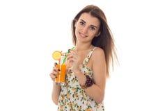 Το νέο όμορφο κορίτσι brunette σε sarafan με το floral σχέδιο πίνει το πορτοκαλί κοκτέιλ και το χαμόγελο στη κάμερα που απομονώνε Στοκ Φωτογραφία