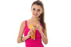 Το νέο όμορφο κορίτσι brunette στο ρόδινο πουκάμισο πίνει το πορτοκαλί κοκτέιλ και το χαμόγελο στη κάμερα που απομονώνεται στο άσ Στοκ εικόνα με δικαίωμα ελεύθερης χρήσης