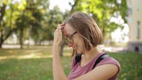 Το νέο όμορφο κορίτσι eyeglasses στα χαμόγελα ευτυχώς στη κάμερα, κλείνει επάνω Θαυμάσια χαμογελώντας γυναίκα με ένα καλό βλέμμα  φιλμ μικρού μήκους