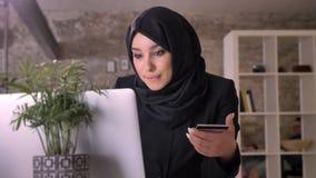 Το νέο όμορφο μουσουλμανικό κορίτσι στο hijab προσέχει στο lap-top και κρατά την πιστωτική κάρτα στην αρχή, έννοια εργασίας, επιχ απόθεμα βίντεο