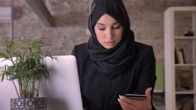 Το νέο όμορφο μουσουλμανικό κορίτσι στο hijab προσέχει στο lap-top και την πιστωτική κάρτα στην αρχή, έννοια εργασίας, επιχειρησι απόθεμα βίντεο