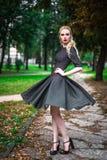 Το νέο όμορφο ξανθό κορίτσι με το κόκκινο κραγιόν στα μεγάλα φωτεινά μάτια της και το κάνει στην τοποθέτηση φορεμάτων στις οδούς, Στοκ Εικόνα
