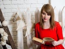 Το νέο όμορφο ξανθό κορίτσι στο κόκκινο φόρεμα διαβάζει ένα βιβλίο σε ένα νέο εσωτερικό έτους ` s Στοκ Φωτογραφίες