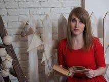 Το νέο όμορφο ξανθό κορίτσι στο κόκκινο φόρεμα διαβάζει ένα βιβλίο σε ένα νέο εσωτερικό έτους ` s Στοκ εικόνα με δικαίωμα ελεύθερης χρήσης