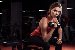 Το νέο όμορφο ξανθό κορίτσι συμμετέχει στον αθλητισμό εκπαιδευτικός με τους αλτήρες στη γυμναστική Πορτρέτο στοκ φωτογραφία με δικαίωμα ελεύθερης χρήσης