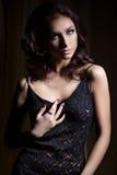 Το νέο όμορφο προκλητικό κορίτσι με ένα ευγενές makeup και η όμορφη τρίχα σε μια μαύρη δαντέλλα ντύνουν με το σκοτεινό φωτισμό στ Στοκ Εικόνες