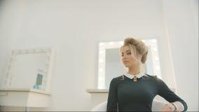 Το νέο όμορφο πρότυπο μετά από αποτελεί και hairdressing συνεδρίαση στην άσπρη καρέκλα Καθρέφτης Makeup με τους βολβούς στο υπόβα απόθεμα βίντεο