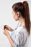 Το νέο όμορφο φίλαθλο κορίτσι ακούει τη μουσική Στοκ Εικόνα