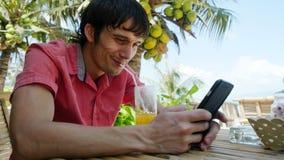 Το νέο όμορφο χαρούμενο άτομο χρησιμοποιεί το έξυπνο τηλέφωνο ενώ έχοντας πίνει το κοκτέιλ σε μια τροπική θέση με τους φοίνικες Στοκ Εικόνες