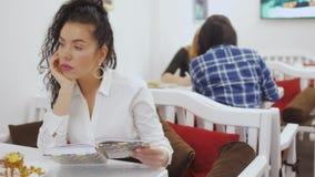 Το νέο όμορφο brunette διαβάζει το βιβλίο στον καφέ και το τρύπημα απόθεμα βίντεο