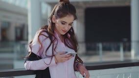 Το νέο όμορφο brunette σε μια καλή διάθεση στο ρόδινο πουκάμισο είναι στο εμπορικό κέντρο Το κορίτσι ένα μήνυμα φιλμ μικρού μήκους