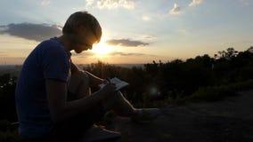 Το νέο blogger γράφει ένα άρθρο σχετικά με έναν χορτοτάπητα στο ηλιοβασίλεμα στην slo-Mo φιλμ μικρού μήκους
