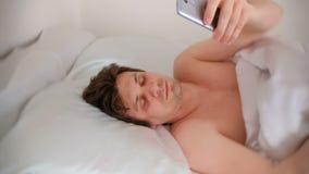Το νέο brunet όμορφο άτομο ξυπνά και κλείνει το συναγερμό στο κινητό τηλέφωνό του απόθεμα βίντεο