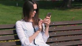 Το νέο brunette γυναικών δακτυλογραφεί ένα μήνυμα στην κινητή τηλεφωνική συνεδρίαση στον πάγκο στο πάρκο απόθεμα βίντεο