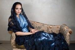 Το νέο brunette σε ένα μπλε σκοτεινό ακρωτήριο φορεμάτων και δαντελλών μεταξιού κάθεται την κλίση στο armrest εκλεκτής ποιότητας  Στοκ Εικόνα