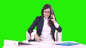 Το νέο brunette σε ένα πράσινο υπόβαθρο κάθεται πίσω από ένα γραφείο στην αρχή και που μιλά στο τηλέφωνο Στον πίνακα είναι έγγραφ φιλμ μικρού μήκους