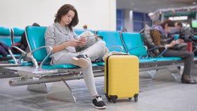 Το νέο brunette χρησιμοποιεί το ελεύθερο wifi σε ένα smartphone στον αερολιμένα περιμένοντας μια τροφή σε ένα αεροπλάνο, η βαλίτσ φιλμ μικρού μήκους