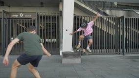 Το νέο hipster κάνει skateboard το τέχνασμα στην ημέρα το καλοκαίρι, το άτομο τον ακολουθεί και κάνει το βίντεο στο smartphone, α φιλμ μικρού μήκους