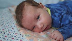 Το νήπιο βρίσκεται στο στομάχι του με τα μεγάλα μάτια ανοικτά σε ένα κρεβάτι για τα νεογνά απόθεμα βίντεο