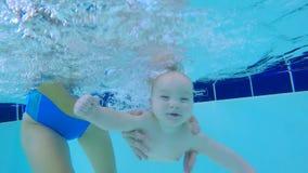 Το νήπιο κολυμπά υποβρύχιο με τη βοήθεια της γυναίκας απόθεμα βίντεο