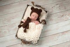 Το νεογέννητο αγοράκι με το καπέλο αρκούδων και το βελούδο αντέχουν το παιχνίδι Στοκ φωτογραφία με δικαίωμα ελεύθερης χρήσης