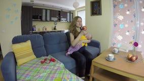 Το νεογέννητο μωρό ταλάντευσης μητέρων σε ετοιμότητα κάθεται στον καναπέ και τρώει το μήλο 4K απόθεμα βίντεο