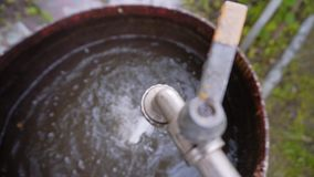 Το νερό από τη βρύση χύνει σε ένα μεγάλο παλαιό σκουριασμένο βαρέλι γεμίζοντας το Υπόλοιπο στη χώρα Η συλλογή του νερού απόθεμα βίντεο