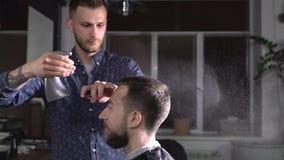 Το νερό παφλασμών κομμωτών από τον ψεκαστήρα στο κεφάλι του επισκέπτη στο barbershop που περιμένει  φιλμ μικρού μήκους