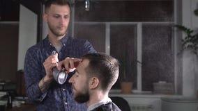 Το νερό παφλασμών κομμωτών από τον ψεκαστήρα στο κεφάλι του επισκέπτη στο barbershop που περιμένει  απόθεμα βίντεο
