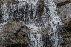 το νερό ρέει αργά κάτω από το βράχο Στοκ Εικόνες