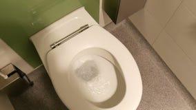 Το νερό στραγγίζεται στον άσπρο κεραμικό θαλαμίσκο τουαλετών της δημόσιας τουαλέτας απόθεμα βίντεο