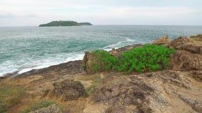 Το νησί μακρυά από το βίντεο ακτών πέρα από το στενό κόλπος θάλασσας ενός τροπικού νησιού κύματα που συντρίβουν ενάντια στην ακτή απόθεμα βίντεο