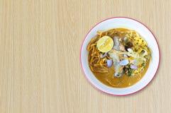 Το νουντλς khao-Soi με το γάλα καρύδων, κοτόπουλο, λεμόνι, παστώνει το ταϊλανδικό ύφος τροφίμων στο ξύλινο υπόβαθρο Στοκ Εικόνες