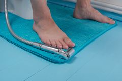 Το ντους για τις οικείες περιοχές πλύσης, μετά από να πάει στην τουαλέτα βρίσκεται στο χαλί, δίπλα στα πόδια στοκ φωτογραφία