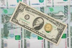 Το νόμισμα είναι εγγραμμένο στο τραπεζογραμμάτιο δέκα δολαρίων που βρίσκεται σε έναν σωρό των χίλιος-ρωσικών τραπεζογραμματίων Στοκ Φωτογραφία