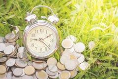 Το νόμισμα και το ξυπνητήρι τοποθετούνται στην πράσινη χλόη, χρήματα, οικονομικά στοκ εικόνες με δικαίωμα ελεύθερης χρήσης