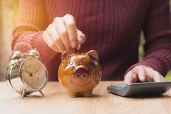 Το νόμισμα σωρών με το χέρι ρίχνει το νόμισμα στη piggy τράπεζα οικονομικός Στοκ εικόνες με δικαίωμα ελεύθερης χρήσης