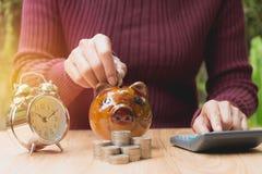 Το νόμισμα σωρών με το χέρι ρίχνει το νόμισμα στη piggy τράπεζα οικονομικός Στοκ Φωτογραφία